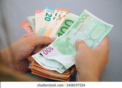 Woman hands that consider 100, 50-euro bills. In the hands of a lot of money, denominations of euros. Businesswoman hands hold and counting euro banknotes.