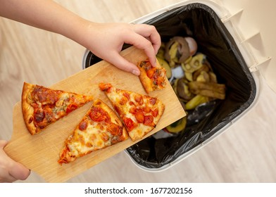 Woman hands throwing food into the trash, bin, waste of food, food concept