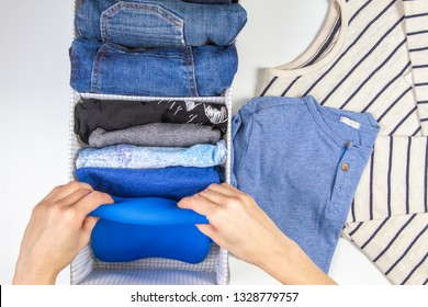 Woman hands tidying up kids clothes in basket. Vertical storage of clothing, tidying up, room cleaning concept