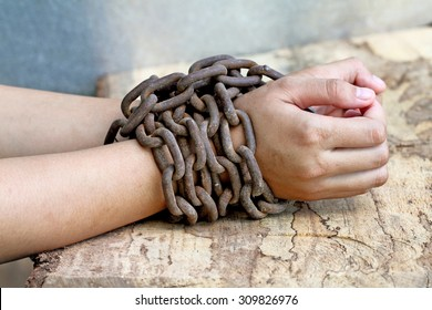 woman hands tied up with chain , Human rights violations concept