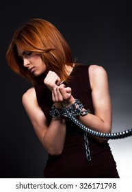 Woman hands tied together with chains.