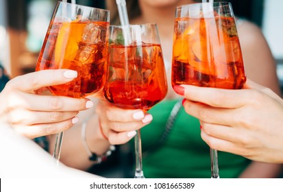 Woman hands toasting with aperol spritz cocktails