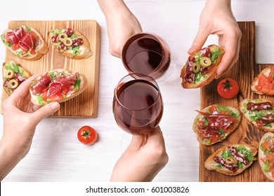Woman hands toasting with glasses of red wine on wooden background