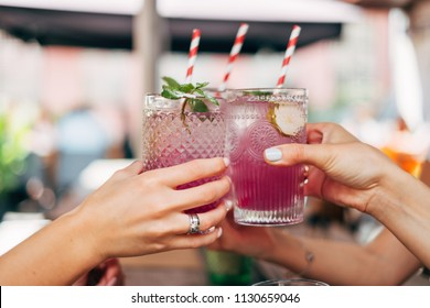Woman hands toasting with iced, colorful summer cocktails