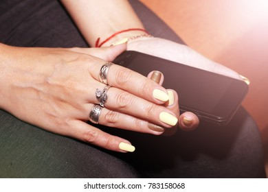 Woman hands touching smartphone bright background, toned