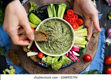 Woman hands try the dipping raw vegan flax bread into Italian pesto sauce in vegetarian healthy buddha bowl with vegetables - tomatoes, cucumbers, spinach, radish, daikon, broccoli. Vegetarian food.