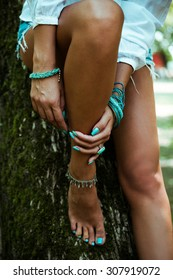 woman hands with turquoise nail polish, ring and bracelets lean on legs, outdoor shot, selective focus