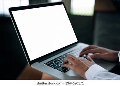 オフィスの膝の上にノートパソコンキーボードを手で打ち、スペースを空けたディスプレイを持つ女性 – 女性のオフィスワーカーとビジネスウーマンのコンセプト