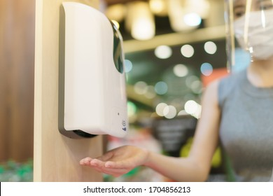 Woman Hands under the automatic alcohol dispenser to avoid the spread of coronavirus.