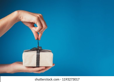 Woman hands unpacking gift box with bow on blue background, copy space