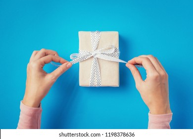 woman hands untie bow on gift box on blue background, top view
