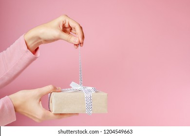 woman hands untie bow on gift box on pink background