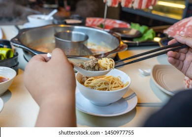 Woman hands using chopsticks and spoon while eating hotpot