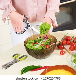 Woman hands using kitchen scissors to cut salad into a salad glass bowl on the kitchen table