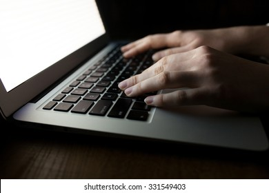 woman hands using laptop at office desk in dark space