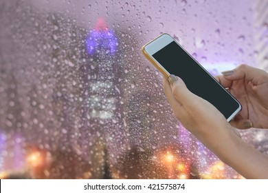 woman hands using mobile phone at glass window with water droplets of raining day at city night view  : business and technology concept