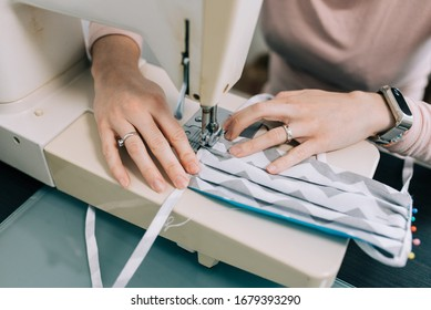 Woman hands using the sewing machine to sew the face medical mask during the coronavirus pandemia. Home made diy protective mask against virus.