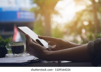 Woman hands using smart phone for work in coffee shop