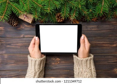 woman hands using tablet computer on wooden table bachground. cristmas shopping time. Happy Christmas mock up background, top view.