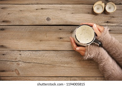 Woman hands in warm sweater embracing of hot coffee mug on rustic wooden table. Top view point.