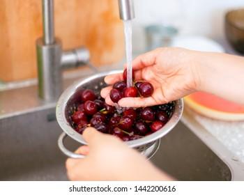 Woman hands washing cherries in colander in the kitchen.