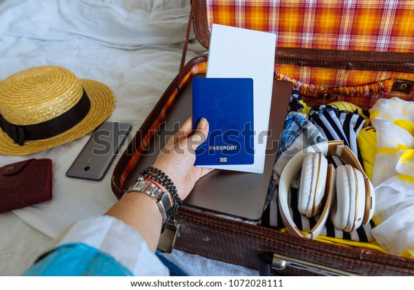 woman hands with watch put clothes in suitcase. travel concept. copy space. biometric passport laptop wallet