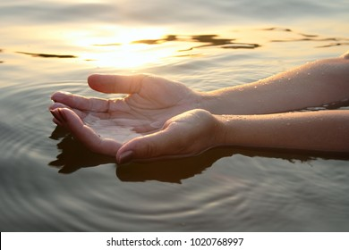 Woman hands in water inviting you over sunset golden rays.