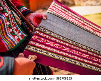 Woman hands weaving artisanal clothing in Peru