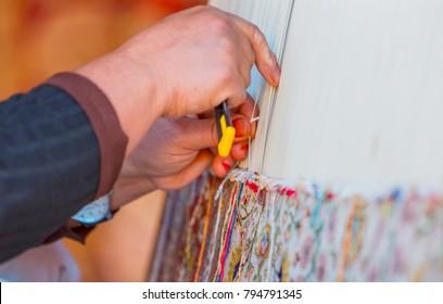Woman hands weaving carpet