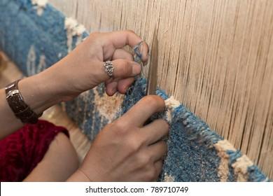 Woman hands weaving carpet on the loom, in Margilan, Uzbekistan.