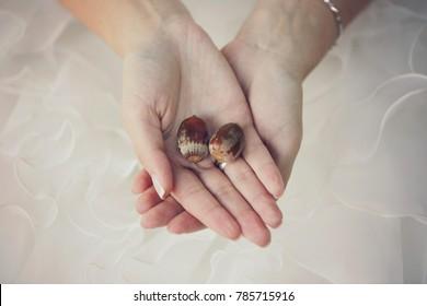 woman hands in wedding dress holding acorns