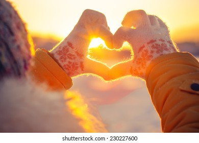 Woman hands in winter gloves Heart symbol shaped Lifestyle and Feelings concept with sunset light nature on background - Shutterstock ID 230227600