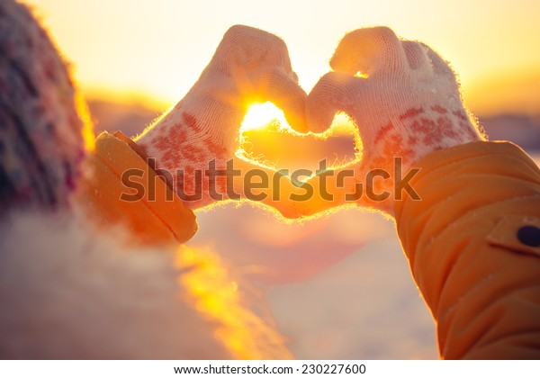 冬の手袋を持つ女性の手ハートのシンボル形のライフスタイルと感情のコンセプトと夕暮れの明るい自然を背景に