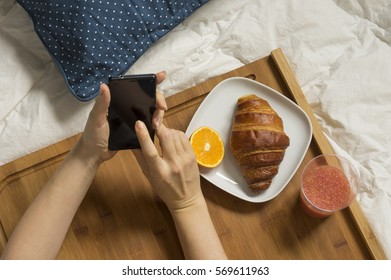Woman hands working with mobile phone at bed and having breakfast