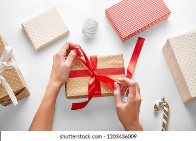 Woman hands wrapping Christmas gift on a white background viewed from above. Top view. Personal perspective