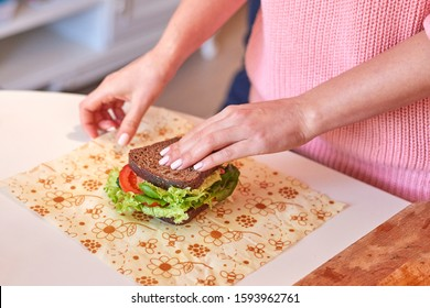 Woman hands wrapping a healthy sandwich in beeswax food wrap. Tomatoes, salad and rye bread. Place for text