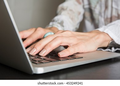 Woman hands writes a pen in a notebook, computer keyboard in background at the home