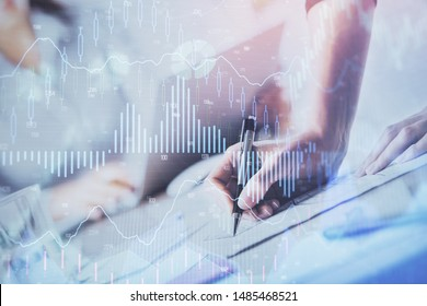 A woman hands writing information about stock market in notepad. Forex chart holograms in front. Concept of research. Double exposure