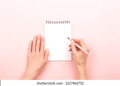 Woman hands are writing on notepad. Beautiful pastel pink background. Copy space for your text.