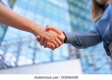 Woman handshaking outdoors over modern glass business building background, close-up picture