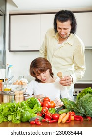 woman and handsome husband cooking with fresh vegetables