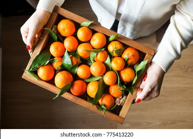 Woman handswith  wooden tray with fresh clementine tangerines top view, copy space