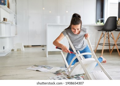 Woman as a handyman at home painting a chair or painting as upcycling