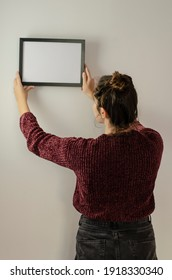 woman hanging black frame with white background