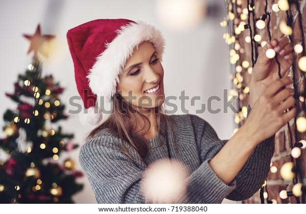 Woman hanging christmas lights at home