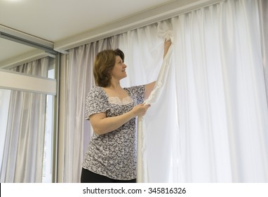Woman hanging up his curtains at the window