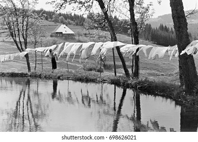Woman hanging laundry by pond