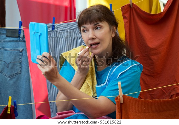 Woman hanging up linen and doing makeup