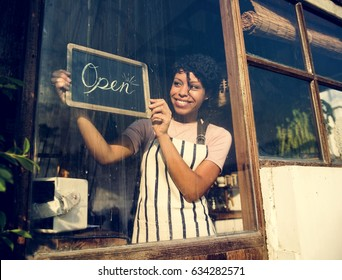 Woman Hanging Open Sign by the Glass Window