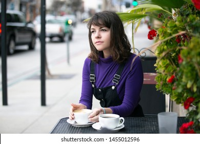 Woman hanging out outdoors and drinking coffee at a side walk cafe or restaurant.  Depicts city life and urban lifestyle.  She is holding a cup while sitting.